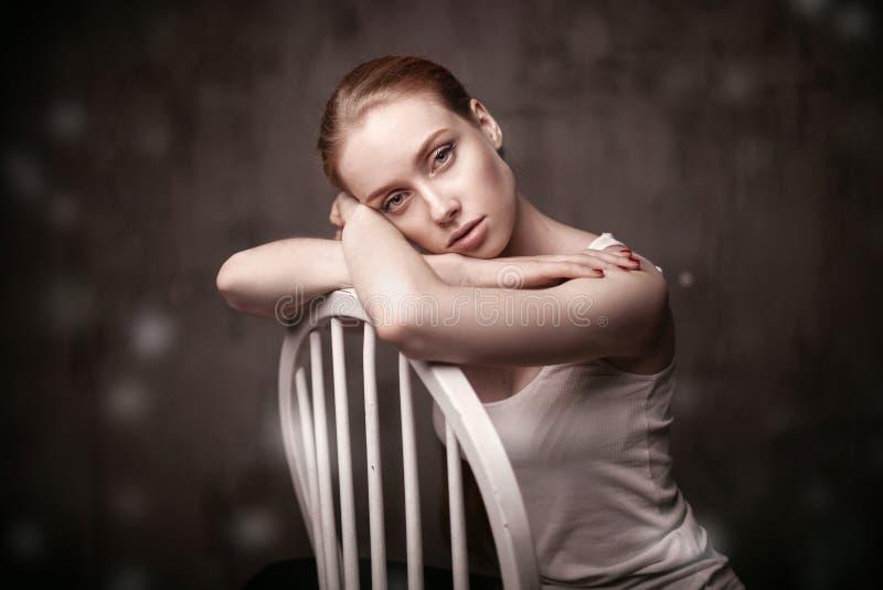 Belle femme s'asseyant sur une chaise blanche image stock