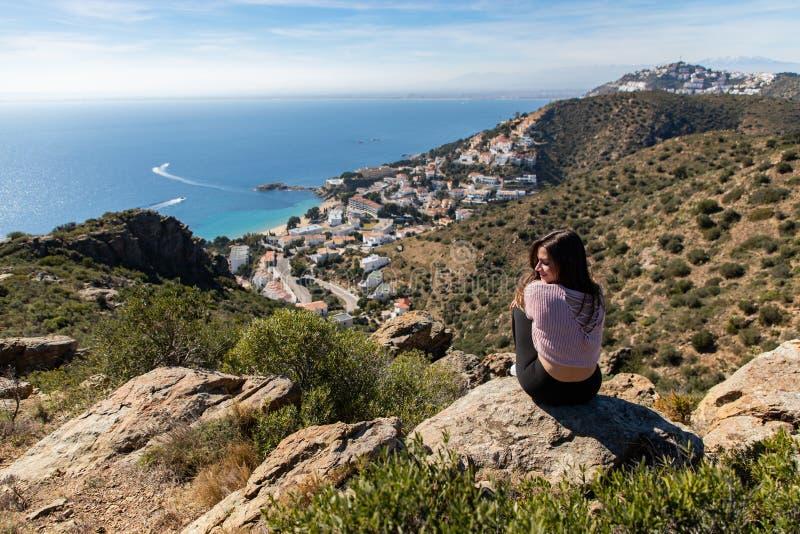 Belle femme s'asseyant sur une falaise avec la mer Méditerranée et la petite ville de côte à l'arrière-plan images libres de droits