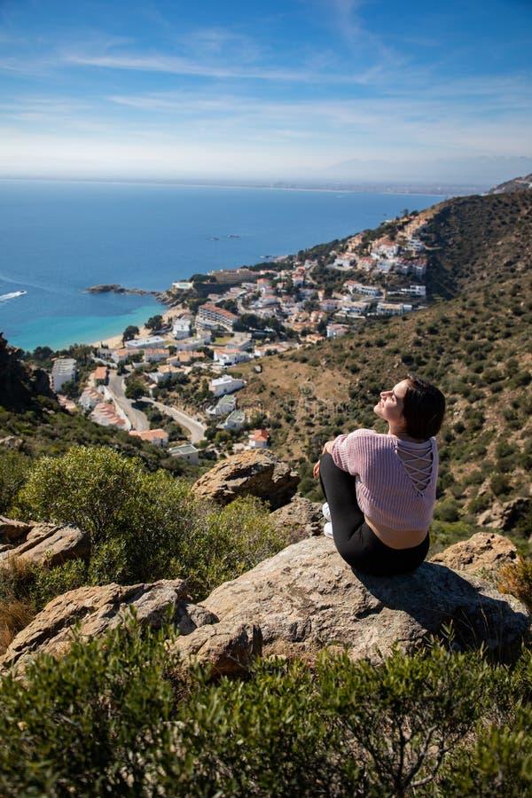 Belle femme s'asseyant sur une falaise avec la mer Méditerranée et la petite ville de côte à l'arrière-plan image stock
