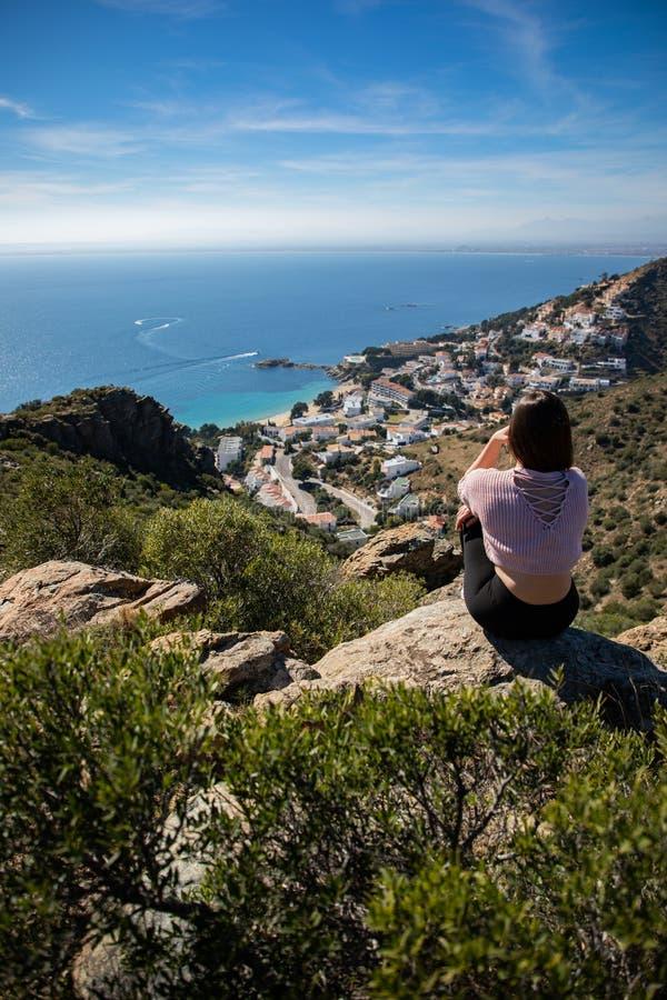 Belle femme s'asseyant sur une falaise avec la mer Méditerranée et la petite ville de côte à l'arrière-plan image libre de droits