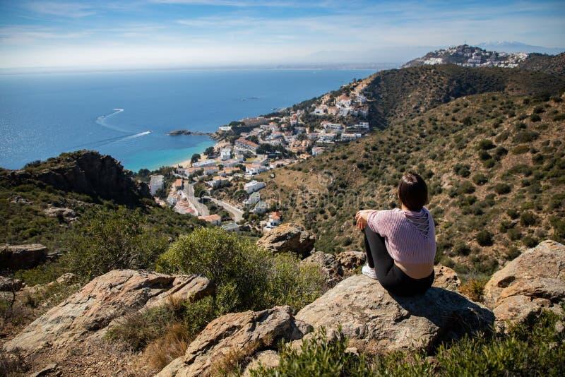 Belle femme s'asseyant sur une falaise avec la mer Méditerranée et la petite ville de côte à l'arrière-plan photographie stock libre de droits