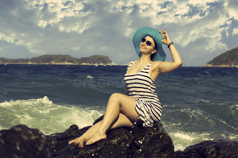 Belle femme s'asseyant sur une pierre et un éclaboussement image stock