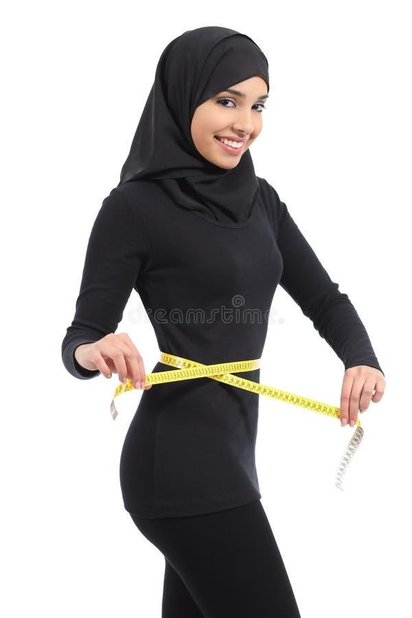 Belle femme saoudienne arabe de forme physique mesurant sa taille avec un ruban métrique photographie stock