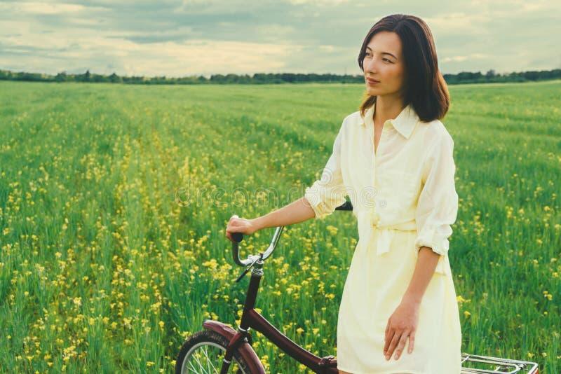 Belle femme se reposant avec une bicyclette sur le pré d'été photos libres de droits