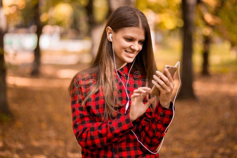 Belle femme se tenant en parc d'automne et à l'aide du téléphone portable photo stock