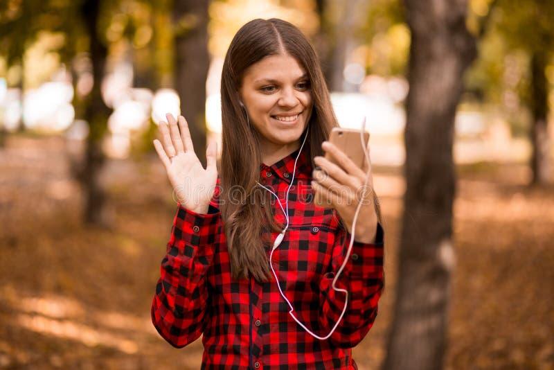 Belle femme se tenant en parc d'automne et à l'aide du téléphone portable image stock