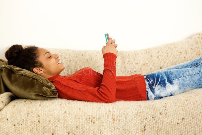Belle femme se trouvant sur le divan avec le téléphone intelligent photo stock
