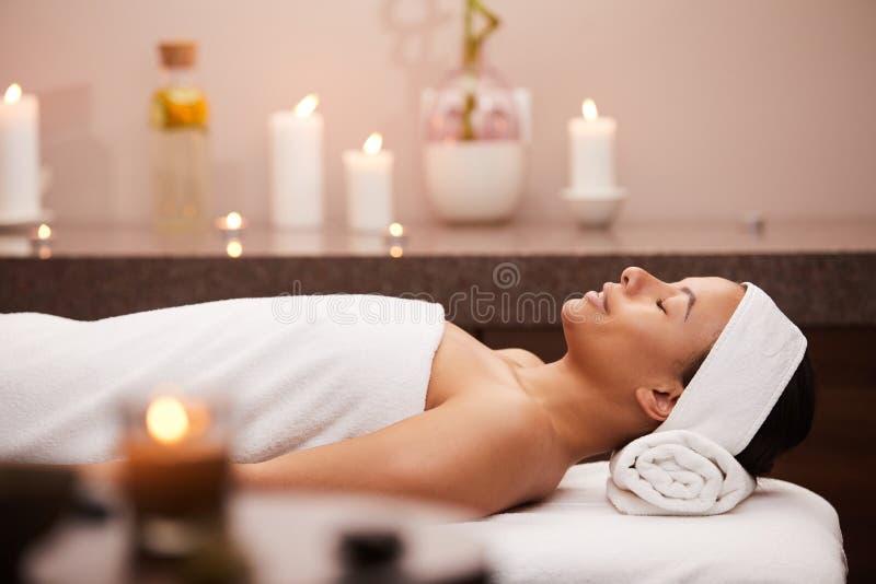 Belle femme se trouvant sur le Tableau de massage photo stock