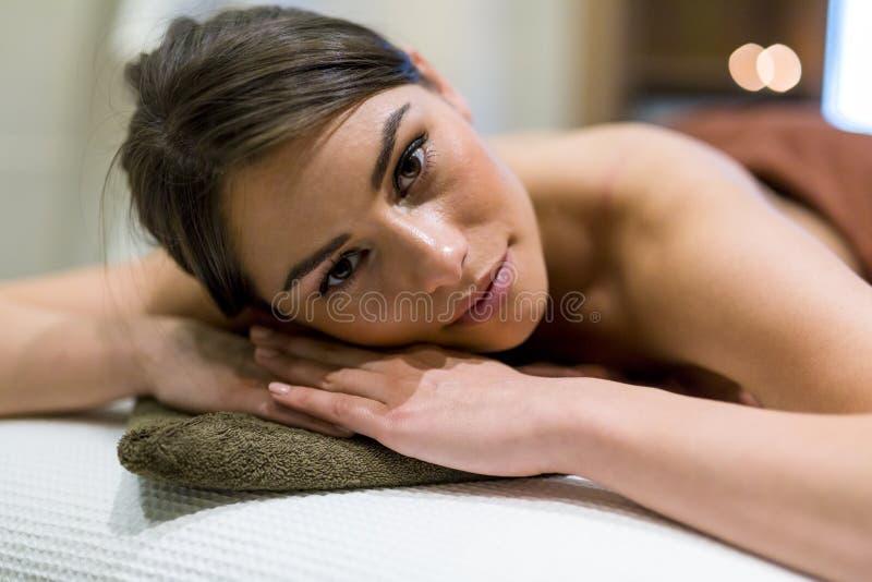 Belle femme se trouvant sur une table et une détente de massage photo stock