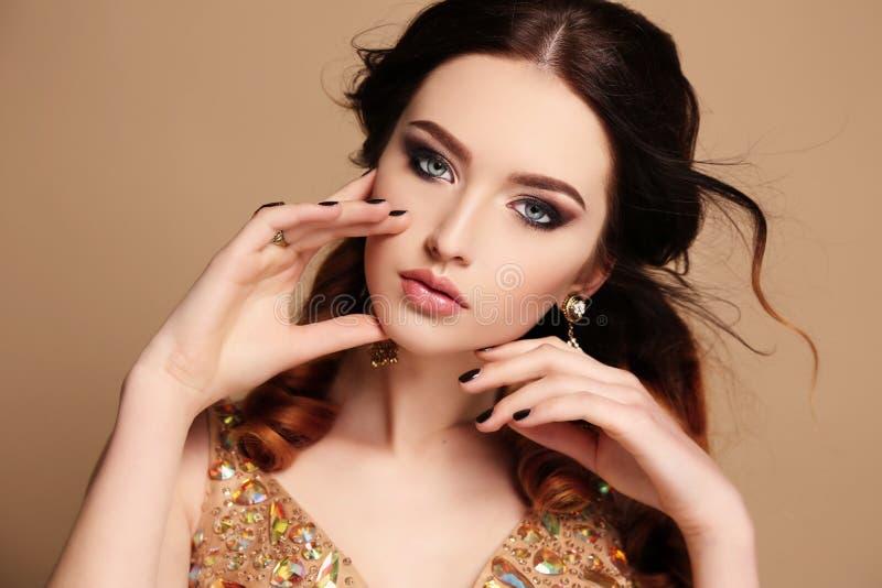 Belle femme sensuelle avec les cheveux foncés et le maquillage lumineux, avec le bijou photographie stock