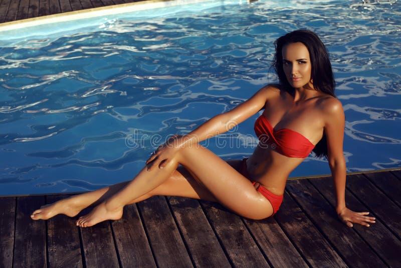 Belle femme sensuelle avec les cheveux foncés utilisant le bikini élégant photo libre de droits