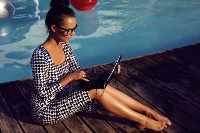 Belle femme sensuelle travaillant sur l'ordinateur dans les vacances photos libres de droits