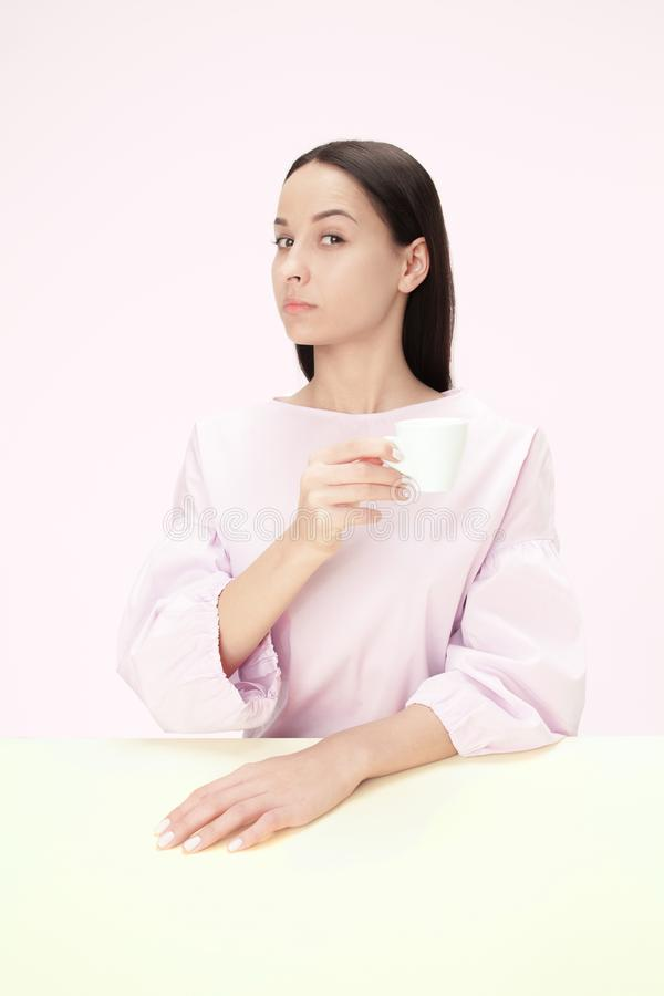 Belle femme seule s'asseyant au studio et semblant triste tenant la tasse de café à disposition Le plan rapproché a modifié la to images stock