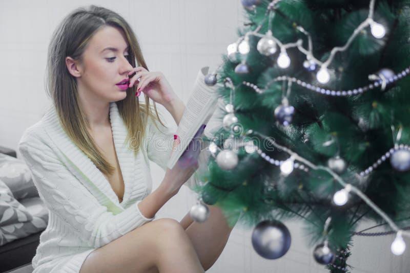 Belle femme sexy avec l'arbre de Noël dans des ouvrages généraux sur le sujet un livre se reposant sur la chaise Portrait de fill photographie stock libre de droits