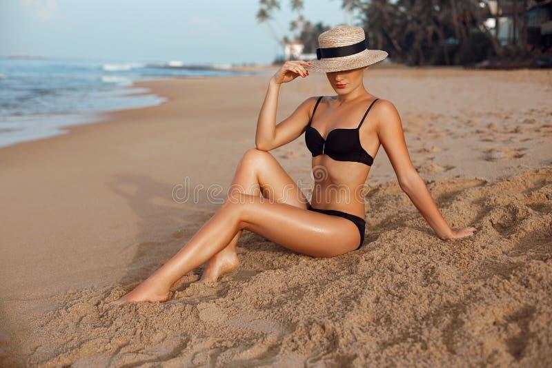 Belle femme sexy avec le corps parfait dans le bikini se trouvant sur la plage Soin de peau Jambes bronzées douces sur la plage images stock