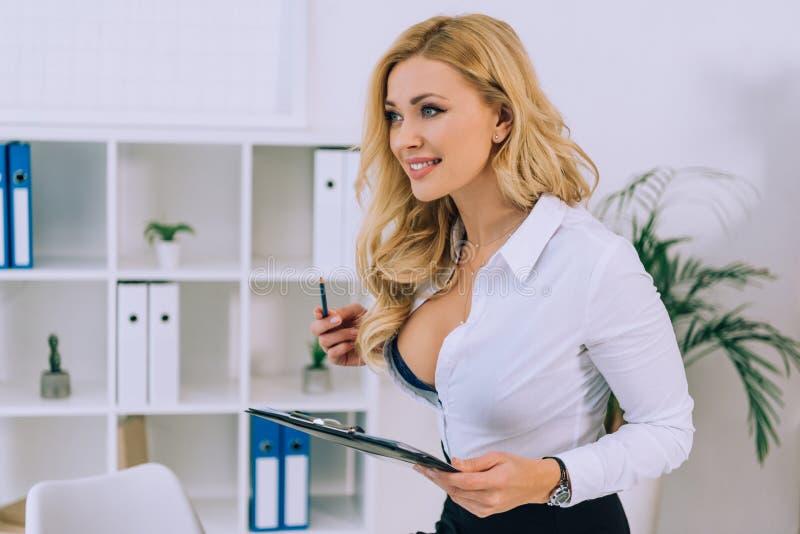 belle femme sexy avec le presse-papiers se tenant decollete images stock