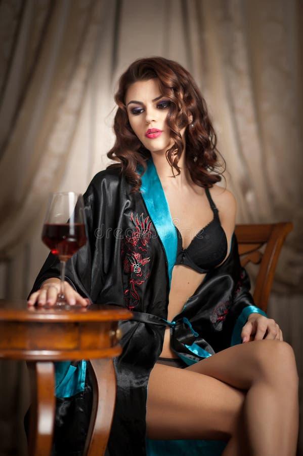 Belle femme sexy avec le verre de vin se reposant sur la chaise. Portrait d'une femme avec de longs cheveux bouclés lançant la rem photo stock
