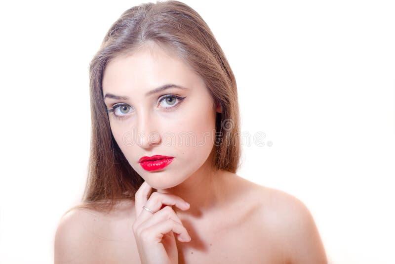 Belle femme sexy avec les lèvres rouges regardant l'appareil-photo sur un portrait blanc de plan rapproché de fond photographie stock libre de droits