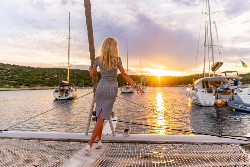 Belle femme sexy dans la robe détendant sur un avant de yacht au coucher du soleil image libre de droits