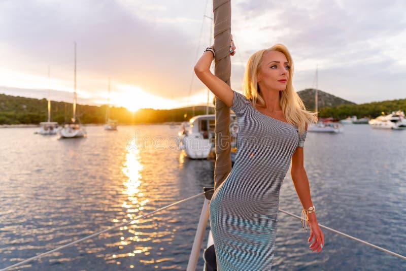 Belle femme sexy dans la robe détendant sur un avant de yacht au coucher du soleil images libres de droits