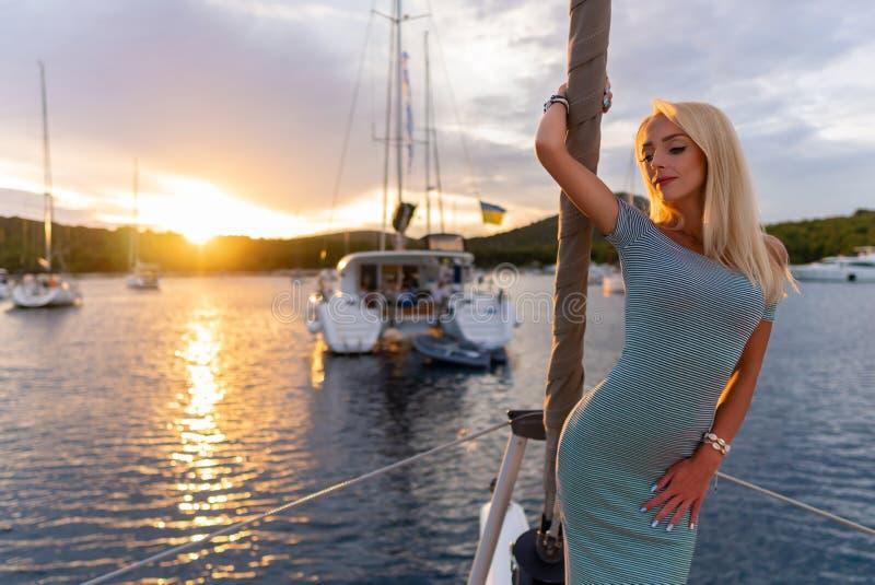 Belle femme sexy dans la robe détendant sur un avant de yacht au coucher du soleil photos libres de droits