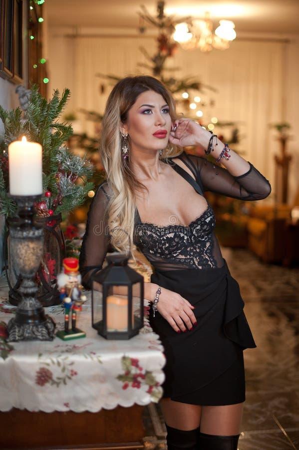 Belle femme sexy dans la robe noire élégante avec l'arbre de Noël à l'arrière-plan Portrait de la pose blonde à la mode de fille  image stock