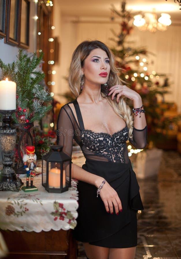 Belle femme sexy dans la robe noire élégante avec l'arbre de Noël à l'arrière-plan Portrait de la pose blonde à la mode de fille  images libres de droits