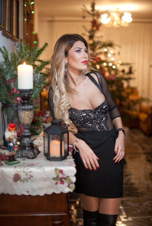 Belle femme sexy dans la robe noire élégante avec l'arbre de Noël à l'arrière-plan Portrait de la pose blonde à la mode de fille  photos libres de droits