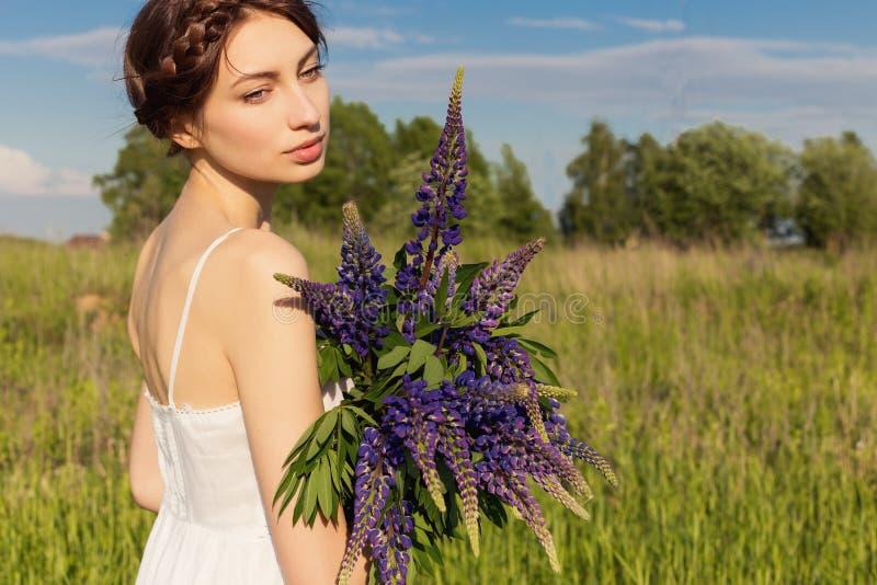 Belle femme sexy dans le bain de soleil blanc avec un bouquet dans les mains de loup dans le domaine au coucher du soleil photographie stock