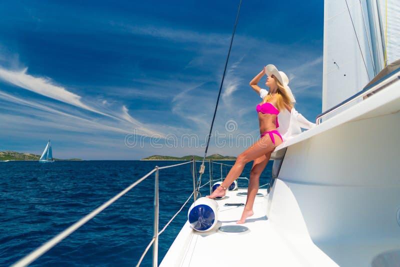 Belle femme sexy dans les vêtements de bain détendant sur un yacht images stock