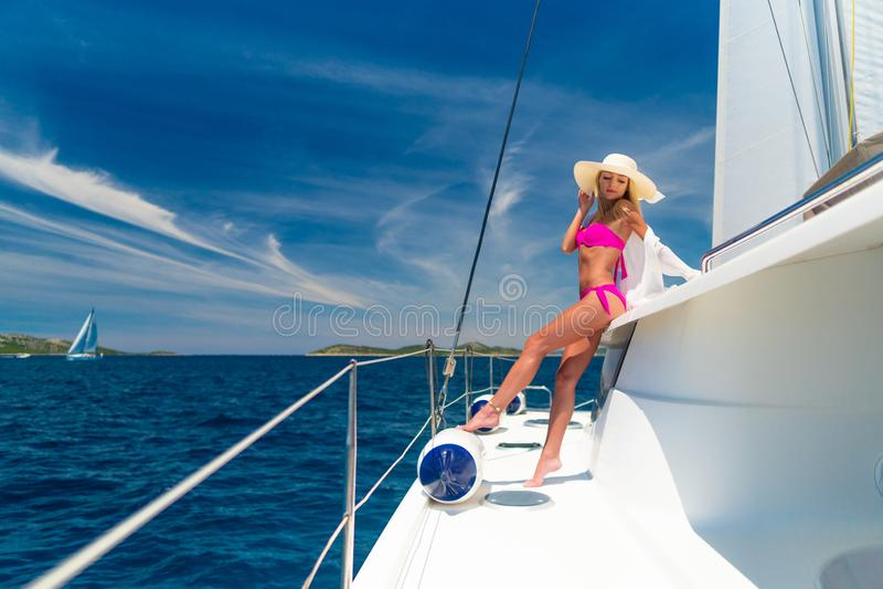 Belle femme sexy dans les vêtements de bain détendant sur un yacht photographie stock libre de droits