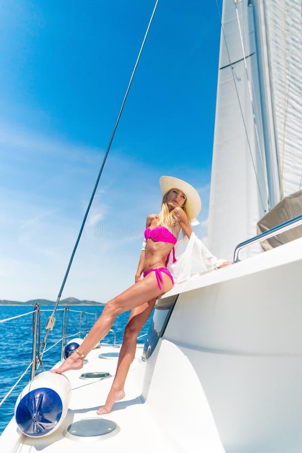 Belle femme sexy dans les vêtements de bain détendant sur un yacht image libre de droits