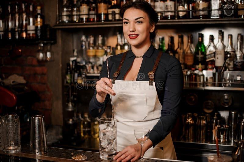 Belle femme sexy de barman remuant la glace dans un verre image stock