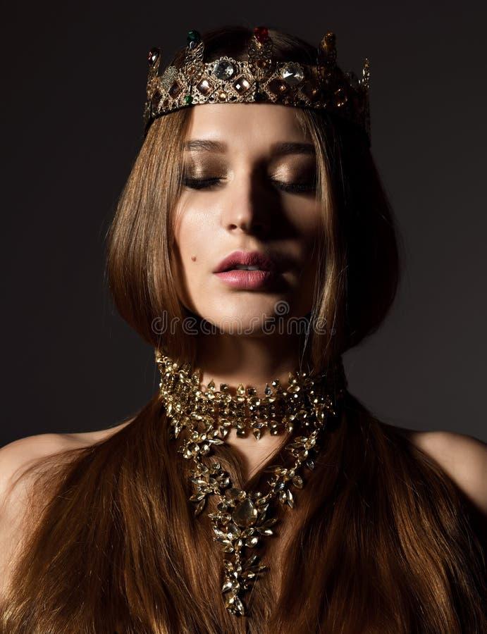 Belle femme sexy de beauté de brune avec la longs couronne et bijoux d'or d'usage de cheveux sur l'obscurité photo libre de droits