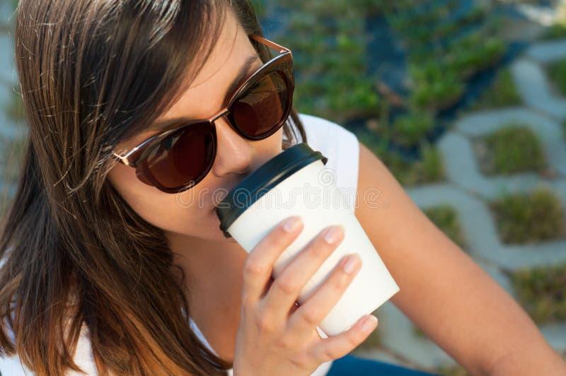 Belle femme sirotant de la tasse de café dehors photo stock