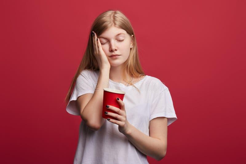 Belle femme somnolente fatiguée tenant le café photo libre de droits