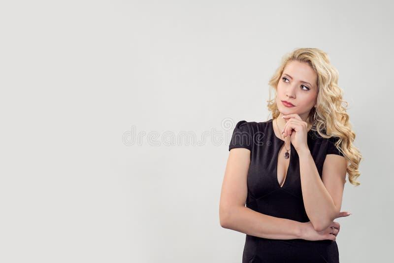 Belle femme songeuse dans la robe noire photo stock