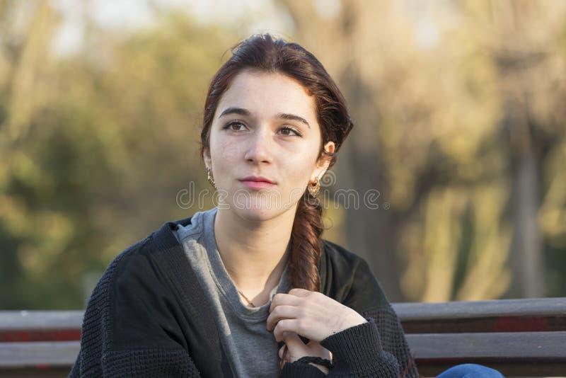 Belle femme songeuse en parc regardant loin photographie stock