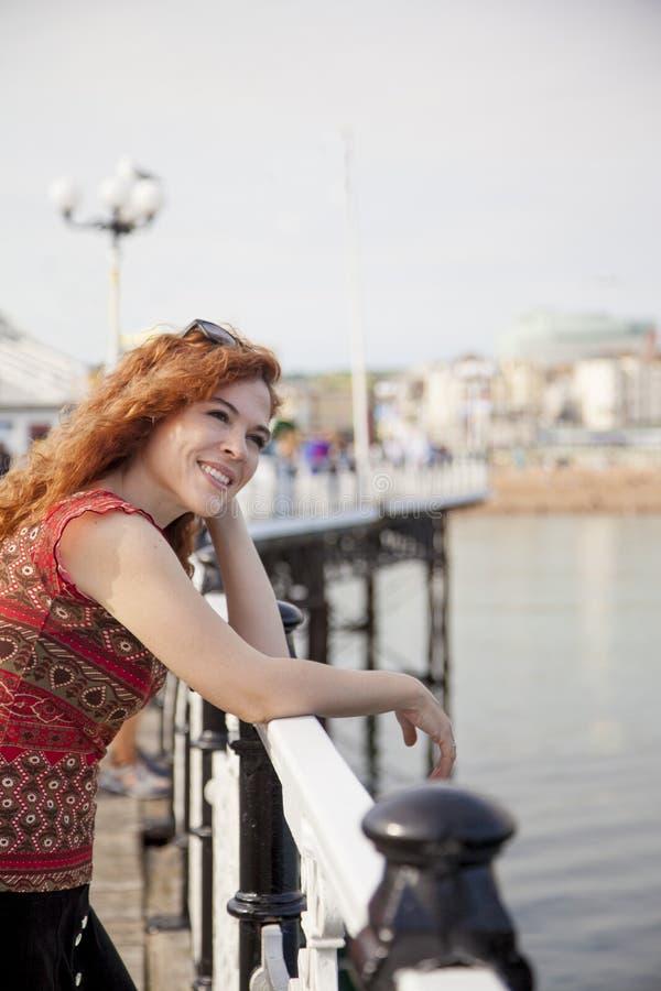Belle femme souriant et se penchant sur une balustrade images libres de droits