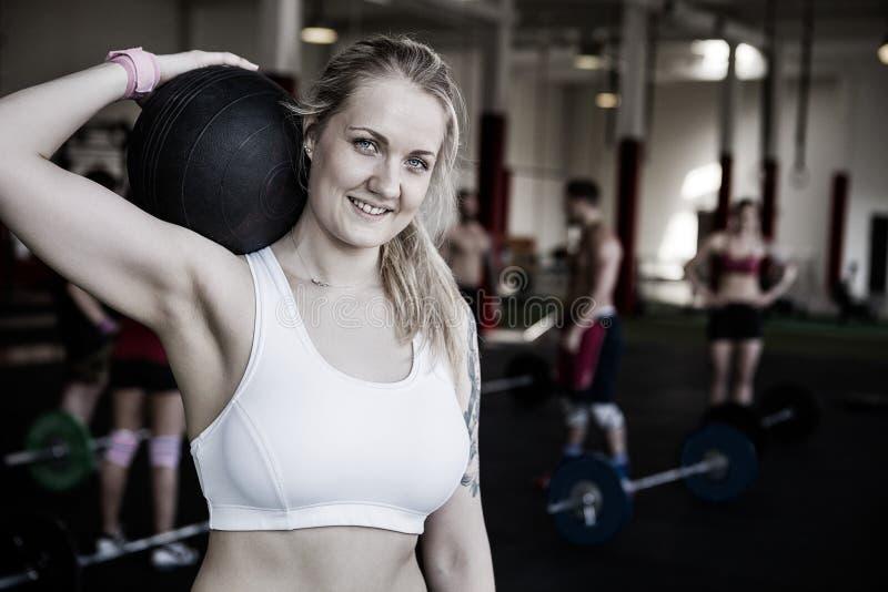 Belle femme souriant tout en s'exerçant avec le medicine-ball photo libre de droits
