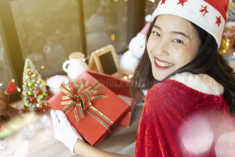 Belle femme souriante avec sa boîte à cadeaux ouverte et accessoires de Noël joyeux décorés dans la chambre image libre de droits