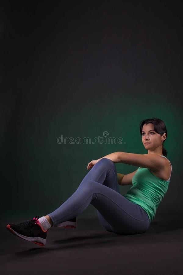 Belle femme sportive faisant l'exercice sur un fond foncé avec le contre-jour vert photos stock