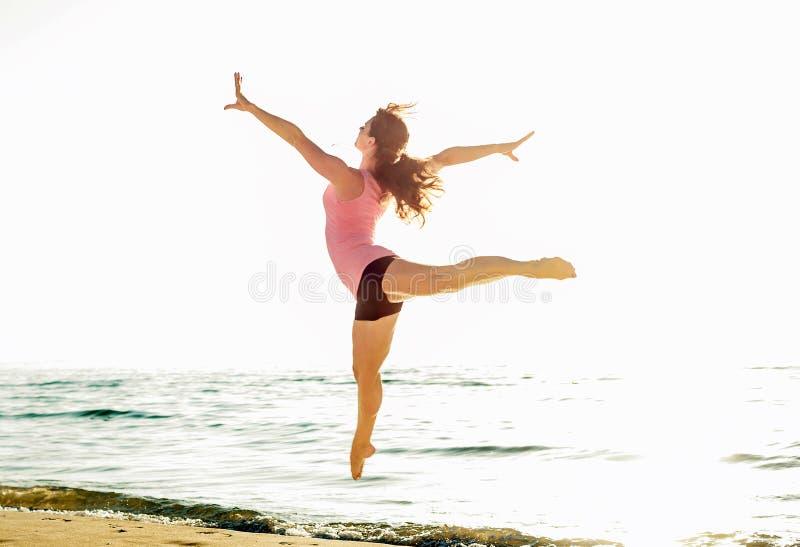 Belle femme sportive sautant sur le bord de la mer, faire femelle de gymnaste image stock
