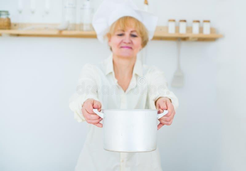 Belle femme supérieure avec un pot en bois à la maison dans la cuisine Foyer sélectif dans la casserole photos stock