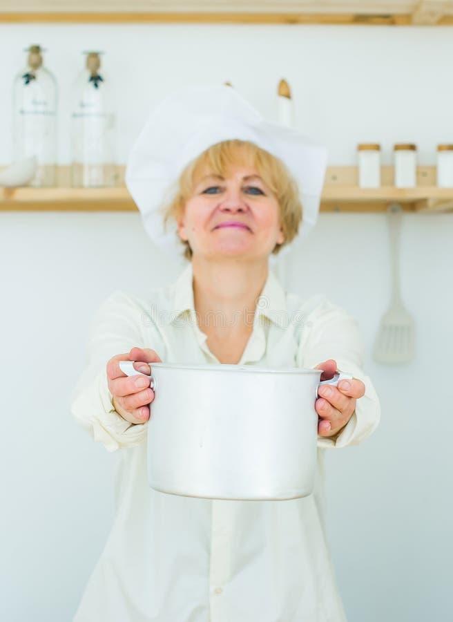 Belle femme supérieure avec un pot en bois à la maison dans la cuisine Foyer sélectif dans la casserole image stock