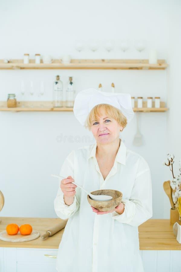 Belle femme supérieure avec un pot en bois à la maison dans la cuisine images libres de droits