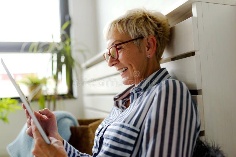 Belle femme supérieure de sourire à l'aide du comprimé numérique à la maison image libre de droits