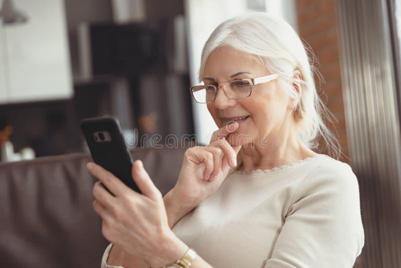 Belle femme supérieure textotant à la maison photo stock