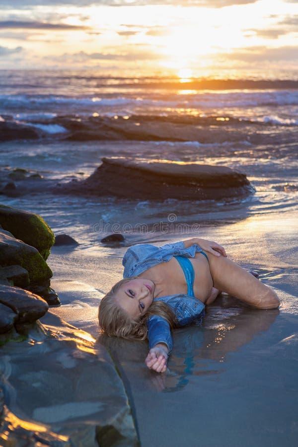 Belle femme sur la c?te au coucher du soleil photos stock