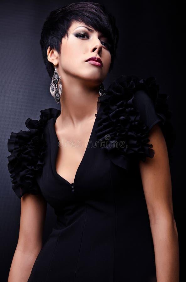 Belle femme sur la pose classique noire de robe dans le studio. images stock